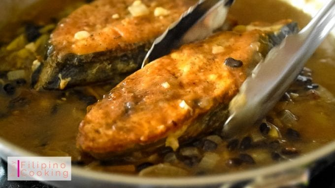 Image of golden brown fish added to thick tausi sauce